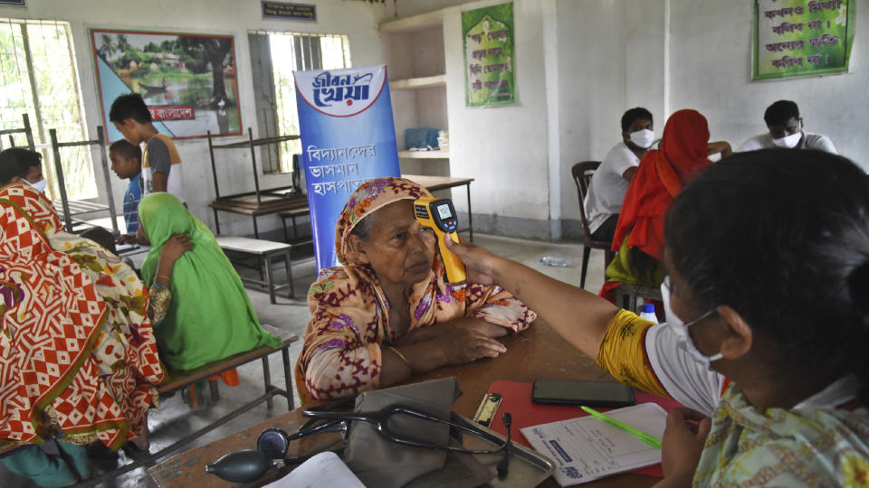 In this photo provided by Bidyanondo Foundation, doctors of boat hospital check patients, in Chandpur district in eastern Bangladesh, on Sept. 12, 2020. A Bangladeshi charity has set up a floating hospital turning a small tourist boat into a healthcare facility to provide services to thousands of people affected by this year's devastating floods that marooned millions. (Bidyanondo Foundation via AP)