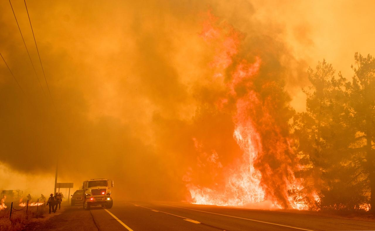 <p>Firefighters scramble to get control as flames from the Pawnee fire jump across highway 20 near Clearlake Oaks, Calif. on July 1, 2018. (Photo: Josh Edelson/AFP/Getty Images) </p>