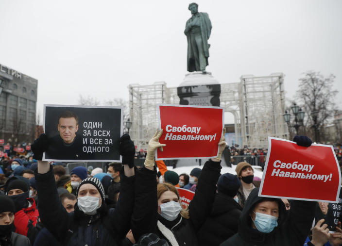 """People gather during a protest against the jailing of opposition leader Alexei Navalny in Pushkin square at the statue of Alexander Pushkin in the background in Moscow, Russia, Saturday, Jan. 23, 2021. Protesters hold posters reading """"Freedom for Navalny!"""" and """"One for all and all for one"""" with Navalny's portrait. Russian police on Saturday arrested hundreds of protesters who took to the streets in temperatures as low as minus-50 C (minus-58 F) to demand the release of Alexei Navalny, the country's top opposition figure. Navalny, President Vladimir Putin's most prominent foe, was arrested on Jan. 17 when he returned to Moscow from Germany, where he had spent five months recovering from a severe nerve-agent poisoning that he blames on the Kremlin. (AP Photo/Pavel Golovkin)"""