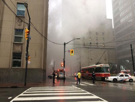 Smoke rises as police block off an intersection in the financial district after reports of a loud blast and heavy smoke could be seen in Toronto, Ontario, Canada May 1, 2017.  REUTERS/Anna Mehler Paperny