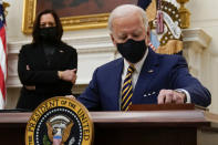 President Joe Biden signs executive orders on the economy in the State Dining Room of the White House, Friday, Jan. 22, 2021, in Washington. Vice President Kamala Harris looks on at left. (AP Photo/Evan Vucci)