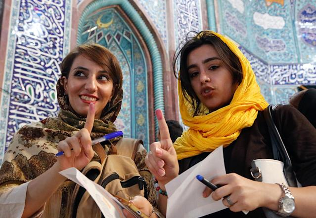 <p>Iranian girls show ink on their fingers after casting their ballot during the Iranian presidential elections at a polling station in Tehran, Iran, May 19, 2017. Out of the candidates, the race is tightest between frontrunners Iranian current president Hassan Rouhani and conservative presidential candidate Ebrahim Raisi. (Photo: Abedin Taherkenareh/EPA) </p>