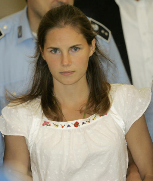 FILE - In this Tuesday Sept. 16, 2008 file photo, then murder suspect Amanda Knox is escorted by Italian penitentiary police officers from Perugia's court after a hearing, central Italy. Few international criminal cases have cleaved along national biases as that of American student Amanda Knox, awaiting half world away her third Italian court verdict in the 2007 slaying of her British roommate, 21-year-old Meredith Kercher. Whatever is decided this week, the protracted legal battle that has grabbed global headlines and polarized trial-watchers in three nations probably won't end in Florence. With the first two trials producing flip-flop guilty-then-innocent verdicts against Knox and her former Italian boyfriend, Raffaele Sollecito, the case has produced harshly clashing versions of events. A Florence appeals panel designated by Italy's supreme court to address errors in the appeals acquittal is set to deliberate Thursday, Jan. 30, 2014, with a verdict expected later in the day .(AP Photo/Antonio Calanni, File)