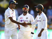 India's Washington Sundar is congratulated by his captain Ajinkya Rahane, right, as Rishabh Pant, centre, watches following play on the first day of the fourth cricket test between India and Australia at the Gabba, Brisbane, Australia, Friday, Jan. 15, 2021. (AP Photo/Tertius Pickard)
