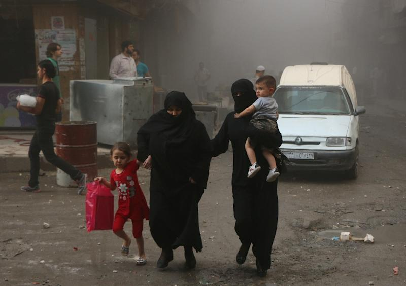 Syrian women and children walk in a dusty street following an air strike by government forces on the rebel held Bustan al-Qasr district in the east of the northern Syrian city of Aleppo on September 20, 2015 (AFP Photo/Baraa al-Halabi)