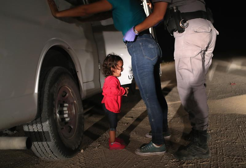 A two-year-old Honduran asylum seeker cries as her mother is searched and detained near the U.S.-Mexico border earlier this month in McAllen, Texas. (John Moore via Getty Images)