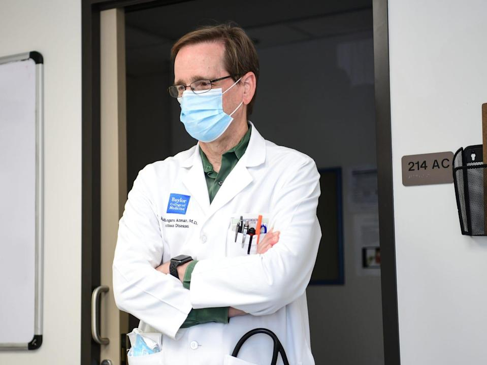 dr. robert atmar stands with his arms crossed and lab coat on