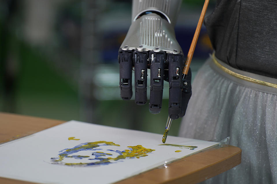 Sophia uses a brush to paint at Hanson Robotics studio in Hong Kong on March 29, 2021. Sophia is a robot of many talents, she speaks, jokes, sings and even makes art. In March, she caused a stir in the art world when a digital work she created as part of a collaboration was sold at an auction for $688,888 in the form of a non-fungible token (NFT). (AP Photo/Vincent Yu)
