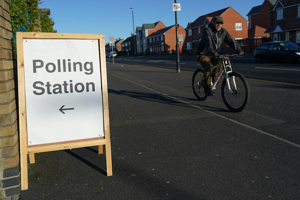 HARTLEPOOL, ENGLAND - MAY 06: A man cycles past a polling station as voting begins in the Hartlepool by-election on May 06, 2021 in Hartlepool, England. Today voters in Hartlepool will decide between returning a Labour Party MP, who has held the seat since its creation in 1974, and the Conservative Party candidate who took a number of Labour's so-called