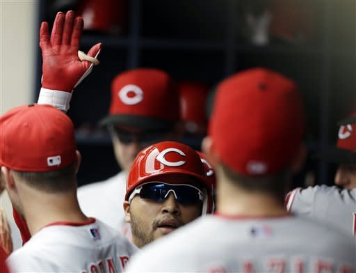 Cincinnati Reds' Dioner Navarro, center, reacts in the dugout after his two-RBI home run against the Milwaukee Brewer in the third inning of a baseball game, Wednesday, Aug. 8, 2012, in Milwaukee. (AP Photo/Jeffrey Phelps)
