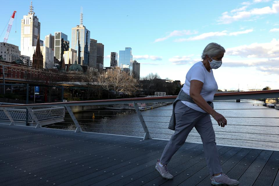A woman wears a face mask as she crosses the Yarra River through an empty bridge in Melbourne. Source: Getty