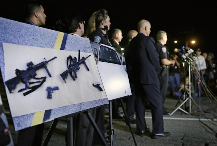 FILE - In this Thursday, Dec. 3, 2015, file photo, police crime photos of assault rifles and handguns are displayed during a news conference near the site of a mass shooting in San Bernardino, Calif. A husband and wife on Dec. 2, 2015, dressed for battle and carrying assault rifles and handguns, opened fire on a holiday banquet for his co-workers, killing at least 14 people and seriously wounding more than a dozen others in a precision assault, authorities said. A federal judge on Friday, June 4, 2021, has overturned California's three-decade-old ban on assault weapons, ruling that it violates the constitutional right to bear arms. (AP Photo/Chris Carlson, File)