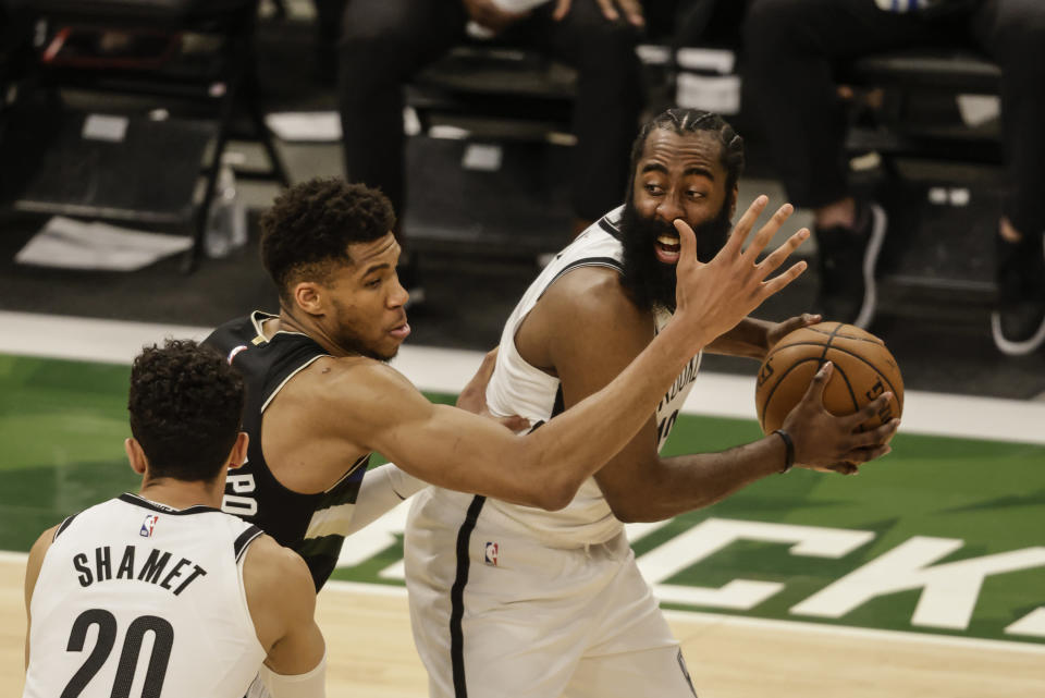 Brooklyn Nets' James Harden, right, is guarded by Milwaukee Bucks forward Giannis Antetokounmpo, center, during the first half of Game 6 of a second-round NBA basketball playoff series Thursday, June 17, 2021, in Milwaukee. (AP Photo/Jeffrey Phelps)