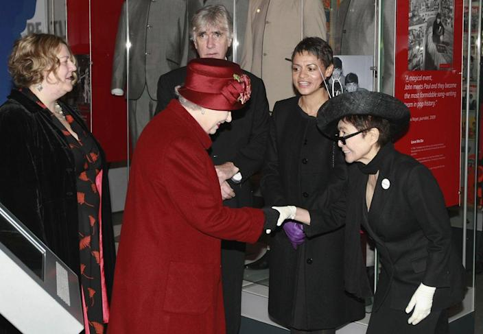 <p>Years after her husband's assassination, Yoko Ono met Queen Elizabeth at the Museum of Liverpool. For the royal occasion, Yoko wore a black suit, hat, and white gloves. </p>