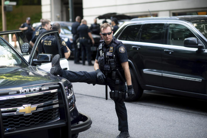 Portland police officer Bonczijk stretches before the start of a protest in Portland, Ore., on Saturday, Aug. 17, 2019. Police have mobilized to prevent clashes between conservative groups and counter-protesters who plan to converge in the city. (AP Photo/Noah Berger)