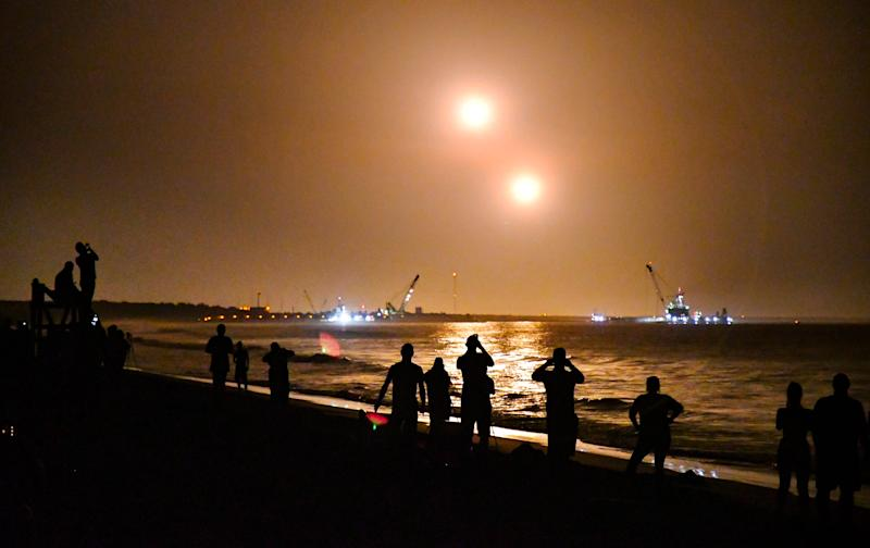 People on the beach near Cherie Down Park in Cape Canaveral watch the boosters land at Cape Canaveral Air Force Station approximately eight minutes after launch.