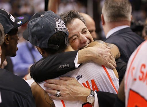 Louisville head coach Rick Pitino (facing camera) hugs his player Peyton Siva after his team defeated Florida 72-68 in an NCAA tournament West Regional final college basketball game on Saturday, March 24, 2012, in Phoenix. (AP Photo/Matt York)