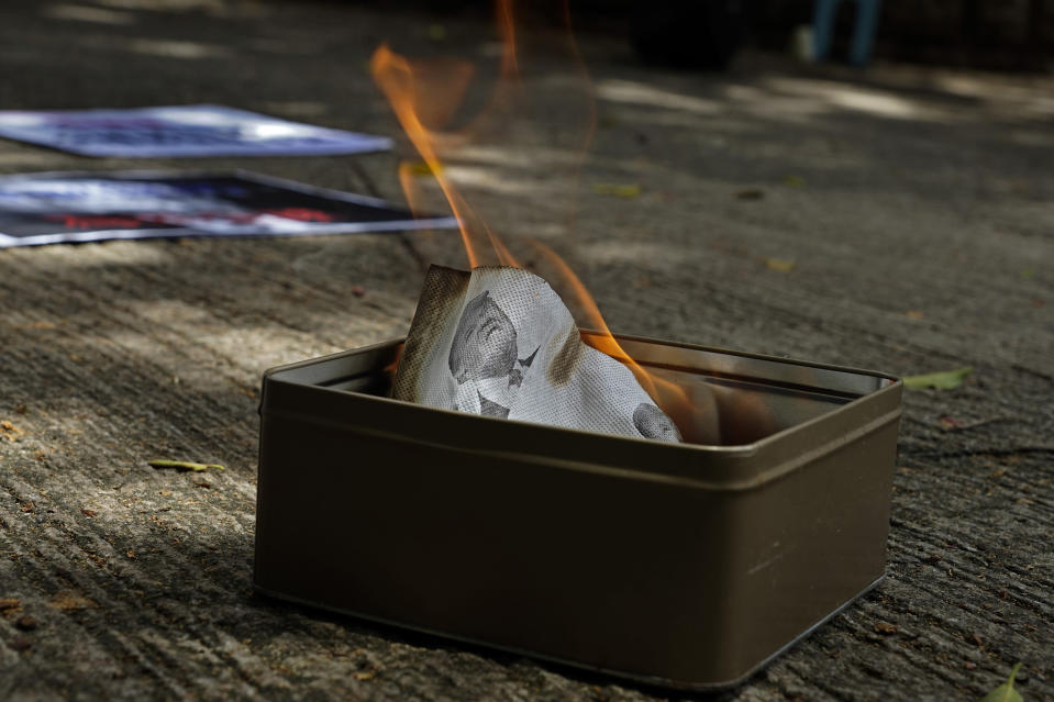 Pro-China supporters burn a picture of U.S. President Donald Trump during a protest against the U.S. sanctions outside the U.S. Consulate in Hong Kong Saturday, Aug. 8, 2020. The U.S. on Friday imposed sanctions on Hong Kong officials, including the pro-China leader of the government, accusing them of cooperating with Beijing's effort to undermine autonomy and crack down on freedom in the former British colony. (AP Photo/Vincent Yu)