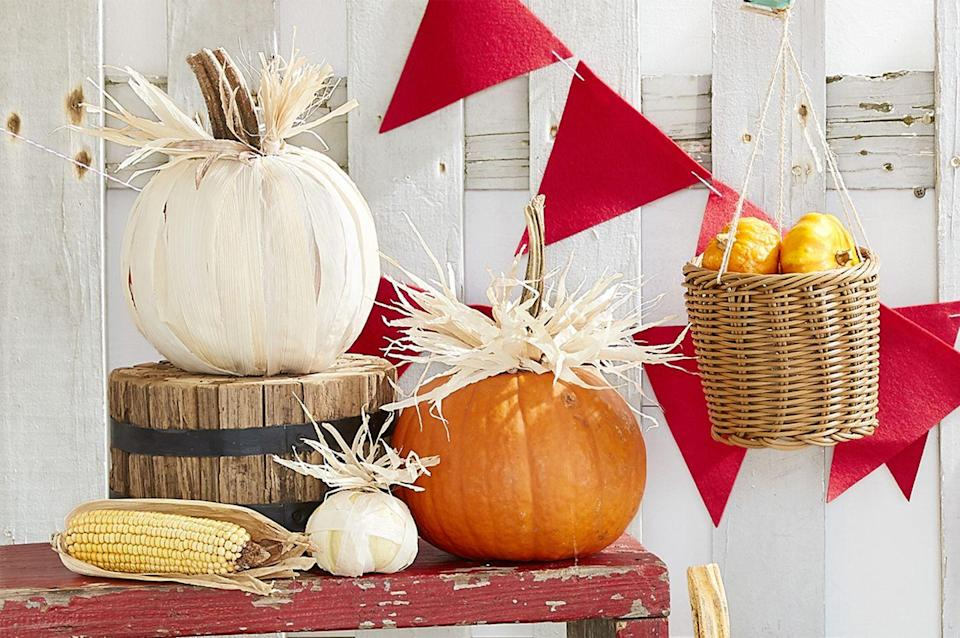 <p>Tamale wrappers or corn husks can transform any average pumpkin into a farmhouse-chic display. To start, tear the wrappers or corn husks into strips, about a quarter to a half-inch wide. Cover a white or orange pumpkin (whichever you'd like!) with strips, hot-gluing in place on the top and bottom. Hot-glue smaller strips around the stems of pumpkins. You'll need about 25 strips for a small pumpkin and 75 for a large pumpkin. </p>