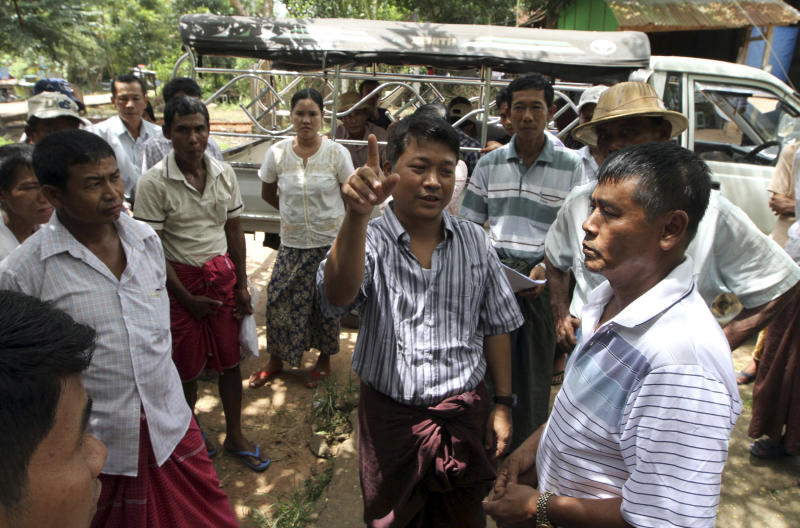In this photo taken on Sept. 15, 2012, Nay Myo Wai, center, chairman of Peace and Diversity party, talks with landless farmers in Yangon, Myanmar. The landscape of Mingaladon township, northern outskirts of Yangon, tells a story of economic upheaval. Skeletons of factories for a new industrial zone rise from thick green rice paddies local farmers say were seized illegally by the Zaykabar Company, one of Myanmar's most powerful companies. Human rights groups say land battles could intensify because companies tied to the military and business elite are rushing to grab land as the country emerges from five decades of isolation and opens its economy. Nay Myo Wai is leading the farmers in their fight against the company. (AP Photo/Khin Maung Win)