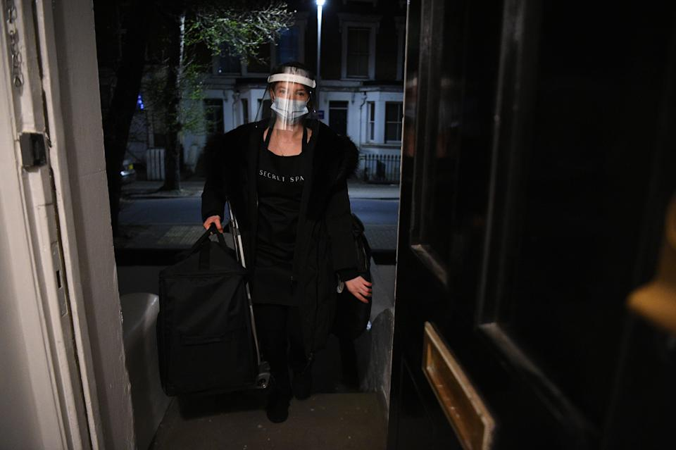 Secret Spa spray tan artist Magdelaine Gibson arrives in Balham, south London, where she has been booked for a midnight appointment to spray tan a group of clients. The five housemates desperate for a trim and tan booked through Secret Spa for stylist Nas Ganev and tan artist Magdelaine Gibson to visit their home at one minute past midnight for haircuts and bronzed skin as coronavirus restrictions eased across England. Secret Spa, which offers at-home beauty and wellness services in London, Manchester and Brighton, have extended their opening hours to accommodate 350 beauty treatments on the first day of restrictions lifting, with the first appointments beginning at one minute past midnight. Picture date: Monday April 12, 2021.
