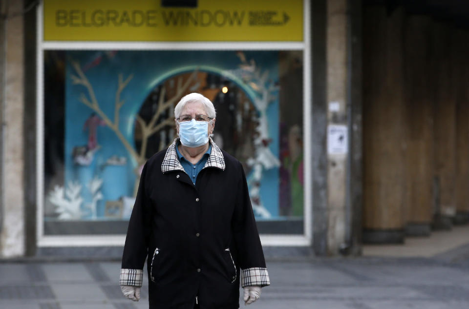 An elderly woman wearing a mask against the spread of the new coronavirus walks during a curfew in downtown Belgrade, Serbia, Tuesday, April 21, 2020. Serbia's elderly on Tuesday ventured outside their homes for the first time in more than a month as the authorities eased some of the strict measures that have been in place against the new coronavirus. Serbia has introduced some of the toughest rules in Europe as part of efforts to curb the spread of the virus. (AP Photo/Darko Vojinovic)