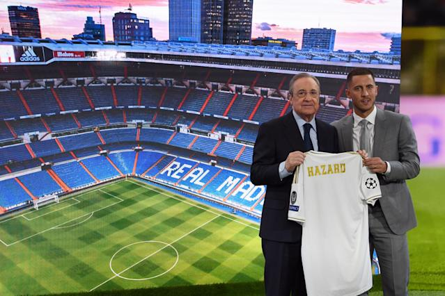 Eden Hazard (R) and Real Madrid president Florentino Perez hold the midfielder's new jersey during his official presentation as new player of the Spanish club at the Santiago Bernabeu stadium in Madrid on June 13, 2019. (Gabriel Bouys/AFP/Getty Images)