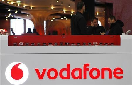 The Vodafone logo is seen at the counter of the shop as customers look at mobile phones in Prague