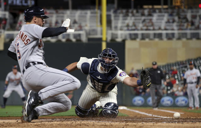 Minnesota Twins catcher Chris Gimenez, right, makes a futile reach for the throw as Detroit Tigers' Nicholas Castellanos slides in to score on a hit by James McCann during the third inning of a baseball game Wednesday, Sept. 26, 2018, in Minneapolis. (AP Photo/Jim Mone)