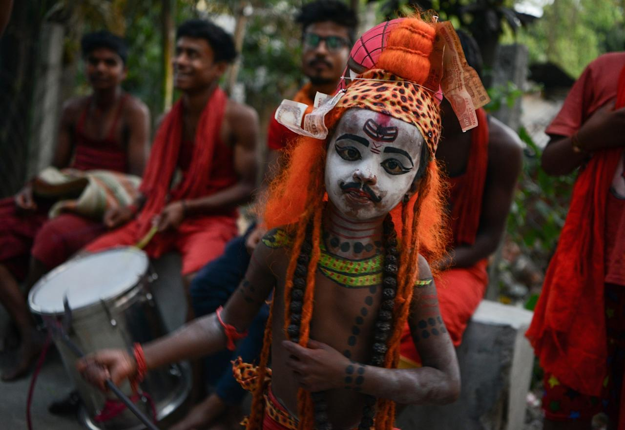 <p>A child dressed as the Hindu deity Shiva dances with others as they begs for alms in Siliguri on the 'Charak' ritual that is observed on the last day of the Bengali calendar year. Hindu devotees offer various symbolic sacrifices hoping for the favour of Shiva to mark the advent of the Bengali new year.<br />DIPTENDU DUTTA / AFP </p>