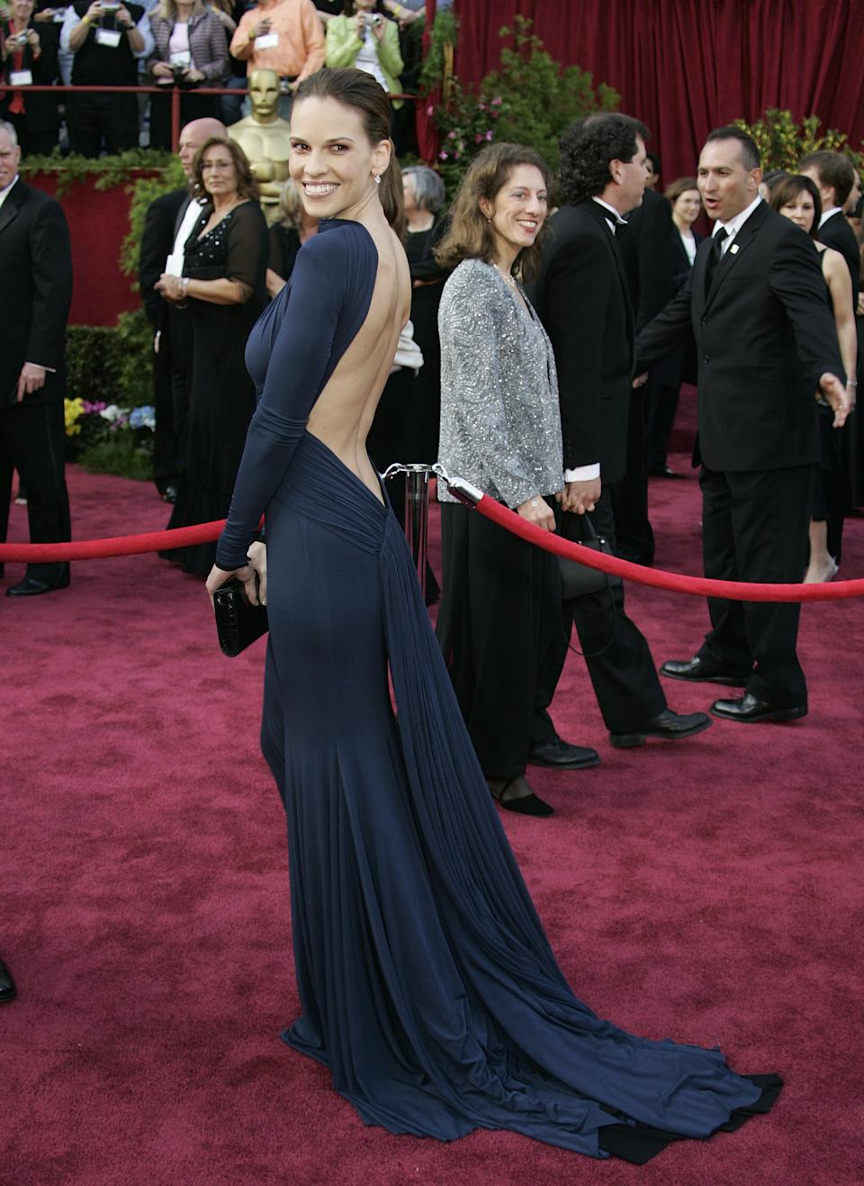 "<p>Swank accepted her second Best Actress Oscar for her role in ""Million Dollar Baby"" in a jaw-dropping navy blue backless gown by French designer Guy Laroche.</p>"