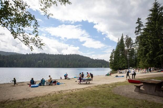 Groups of up to 10 people are now allowed to socialize outdoors in B.C., as long as members of different families keep their distance from each other. People are pictured at Sasamat Lake in Port Moody last July when COVID-19 cases were lower.  (Ben Nelms/CBC - image credit)