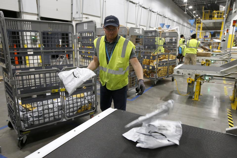 In this Dec. 17, 2019, photo Steven Smith places packages onto a conveyor prior to Amazon robots transporting packages to chutes that are organized by zip code, at an Amazon warehouse facility in Goodyear, Ariz. (AP Photo/Ross D. Franklin)