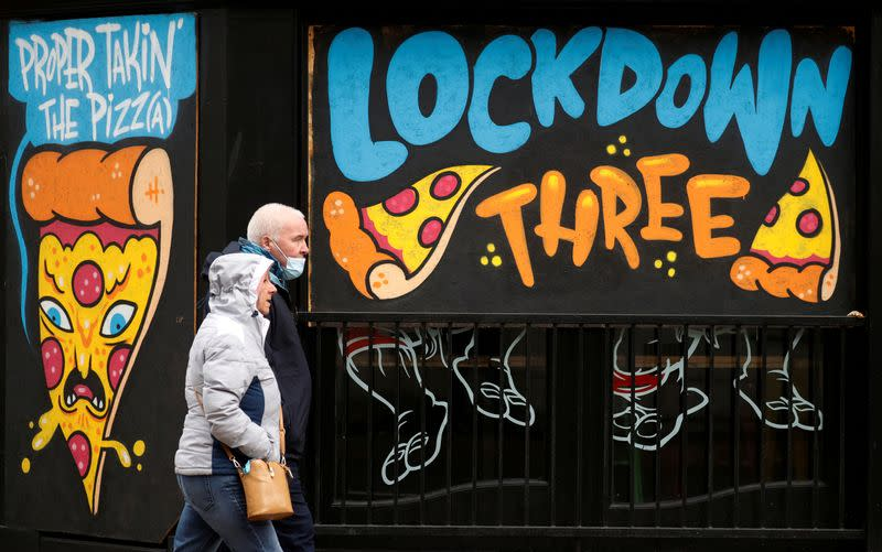 FILE PHOTO: People walk past a mural amid the outbreak of the coronavirus disease (COVID-19) in Manchester