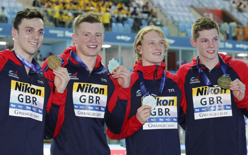 Britain's men's 4x100m medley relay team, from left, Luke Greenbank, Adam Peaty, James Guy and Duncan Scott pose with their gold medals at the World Swimming Championships in Gwangju, South Korea, Sunday, July 28, 2019. (AP Photo/Lee Jin-man)