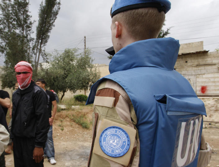 In this picture taken during a UN observer-organized tour, an anti-Syrian regime man, left, his face covered to obscure his identity, looks at a UN observer in Hama city, central Syria, on Thursday, May 3, 2012. Syrian security forces stormed dorms at a northwestern university to break up anti-government protests there, killing at least four students and wounding several others with tear gas and live ammunition, activists and opposition groups said Thursday. (AP Photo/Muzaffar Salman)