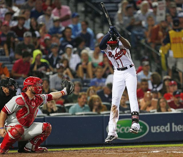 Atlanta Braves' B.J. Upton avoids being hit with a pitch as Philadelphia Phillies catcher Cameron Rupp makes the catch in the fourth inning of a baseball game in Atlanta, Friday, July 18, 2014. (AP Photo/John Bazemore)