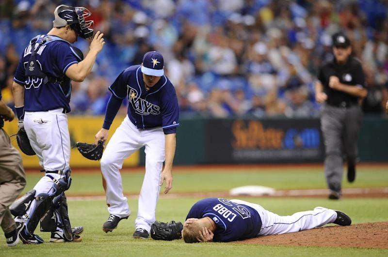 Tampa Bay Rays catcher Jose Lobaton, left, and left fielder Kelly Johnson, center, rush in to assist starting pitcher Alex Cobb as Cobb grabs his head and lies on the pitcher's mound after being hit by a line drive by Kansas City Royals' Eric Hosmer during the fifth inning of a baseball game Saturday, June 15, 2013, in St. Petersburg, Fla. Cobb was taken off the field on a stretcher. (AP Photo/Brian Blanco)