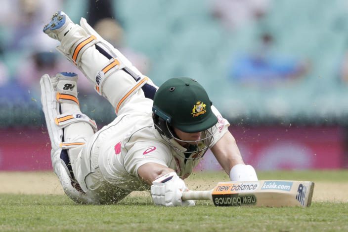 Australia's Steve Smith dives to make his ground but is run out for 131 runs during play on day two of the third cricket test between India and Australia at the Sydney Cricket Ground, Sydney, Australia, Friday, Jan. 8, 2021. (AP Photo/Rick Rycroft)