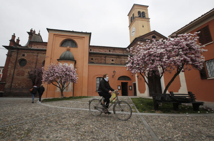 In this photo taken on Thursday, March 12, 2020, a woman wearing a mask rides a bicycle in Codogno, Italy. The northern Italian town that recorded Italy's first coronavirus infection has offered a virtuous example to fellow Italians, now facing an unprecedented nationwide lockdown, that by staying home, trends can reverse. Infections of the new virus have not stopped in Codogno, which still has registered the most of any of the 10 Lombardy towns Italy's original red zone, but they have slowed. For most people, the new coronavirus causes only mild or moderate symptoms. For some it can cause more severe illness. (AP Photo/Antonio Calanni)