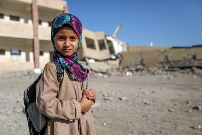 A Yemeni girl stands outside a school on March 16, 2017 that was damaged in an air strike in the southern city of Taez (AFP Photo/Ahmad AL-BASHA)