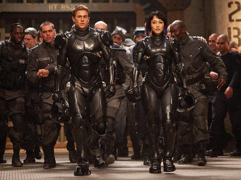 """This publicity photo released by Warner Bros. Pictures shows, front from left, Charlie Hunnam as Raleigh Becket and Rinko Kikuchi as Mako Mori in a scene from, """"Pacific Rim."""" (AP Photo/Warner Bros. Pictures, Kerry Hayes)"""