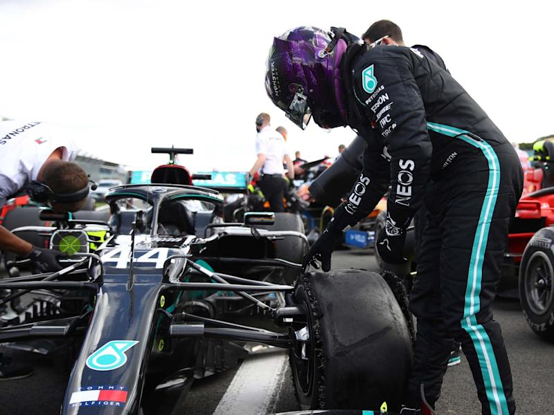 Lewis Hamilton inspects his damaged Mercedes after winning the British Grand Prix: AP
