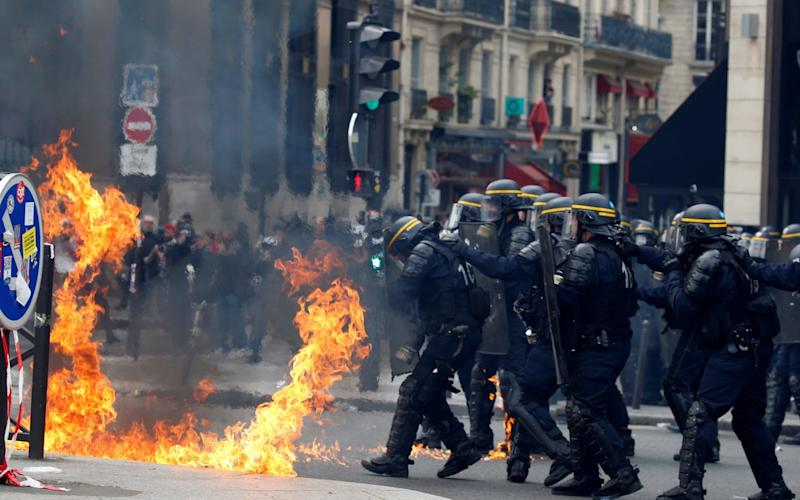 French CRS riot police protect themselves from flames during clashes - Credit: Reuters