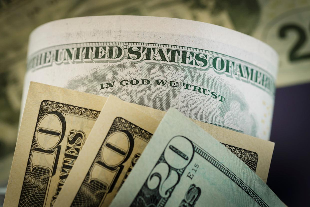 """The phrase """"In God We Trust,"""" seen on a U.S. dollar bill, became the national motto in 1956. (Photo: Thomas Trutschel via Getty Images)"""