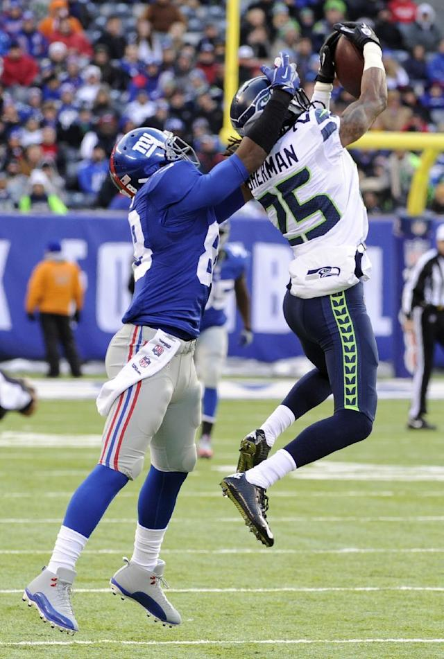Seattle Seahawks cornerback Richard Sherman, right, intercepts a pass from New York Giants quarterback Eli Manning intended for wide receiver Hakeem Nicks, left, during the first half of an NFL football game on Sunday, Dec. 15, 2013, in East Rutherford, N.J. (AP Photo/Bill Kostroun)