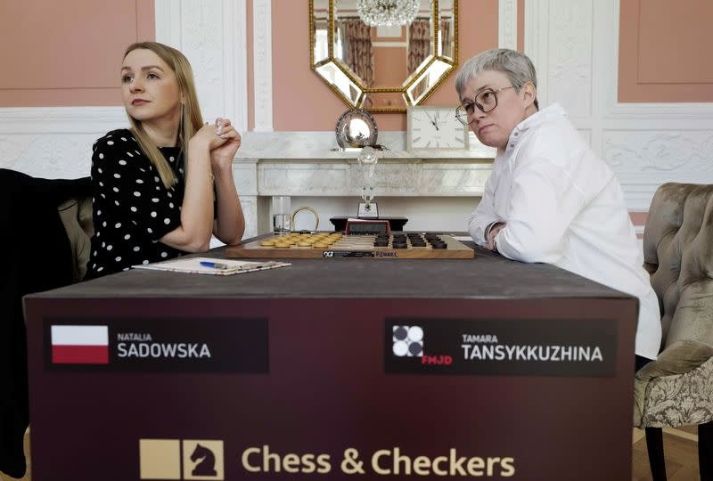 Draught players Polish Natalia Sadowska and Russian Tamara Tansykkuzhina look on before a game during the Women's World Draughts Championship in Warsaw