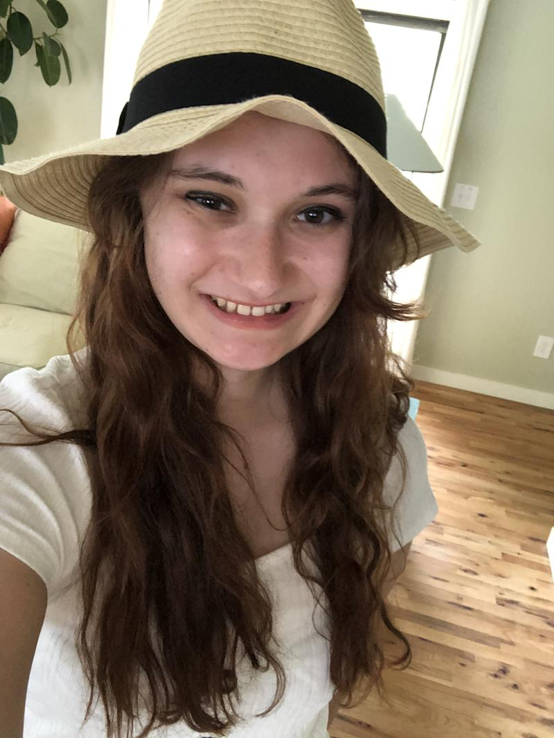 Kelly wearing a straw hat and smiling.