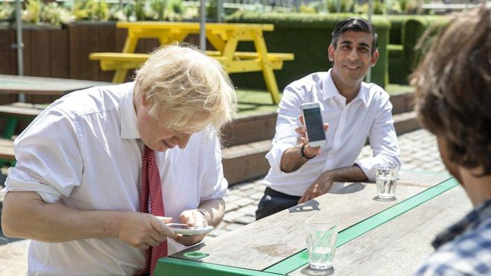 Prime Minister Boris Johnson (left) and British Prime Minister Rishi Sunak (right) will use their smartphones to visit a pizza pilgrim at the West India Pier in London Docklands on June 26, 2020.
