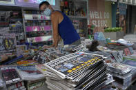 A vendor adjusts copies of Apple Daily at a news stand at a downtown street in Hong Kong Friday, June 18, 2021. The pro-democracy paper increased its print run to 500,000 copies on Friday, a day after police arrested five top editors and executives and froze $2.3 million in assets linked to the media company. (AP Photo/Vincent Yu)